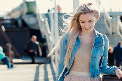Young cheerful girl on the seashore. Young blonde woman smiling. Trendy style. Young cheerful girl on the seashore. Young blonde woman smiling Royalty Free Stock Photo