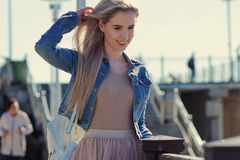 Young cheerful girl on the seashore. Young blonde woman smiling. Trendy style. Young cheerful girl on the seashore. Young blonde woman smiling Stock Photo