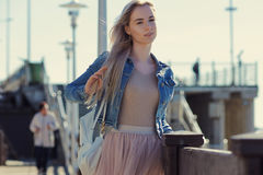 Young cheerful girl on the seashore. Young blonde woman smiling. Trendy style. Young cheerful girl on the seashore. Young blonde woman smiling Stock Image