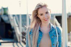 Young cheerful girl on the seashore. Young blonde woman smiling. Trendy style. Young cheerful girl on the seashore. Young blonde woman smiling Royalty Free Stock Photography
