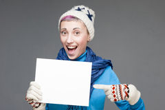 Young cheerful girl with sign on gray background. Studio portrait of young cheerful short-cutted blond caucasian girl in winter clothing pointing on sign on gray Royalty Free Stock Images