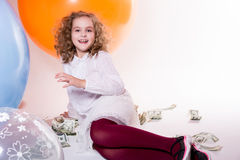 Young cheerful girl sitting and lying around dollars and big rub Royalty Free Stock Photos