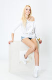 Young, cheerful girl sitting on a white square,  on white Royalty Free Stock Photos