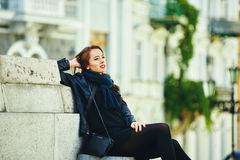 Young cheerful girl smiling posing on the steps of city street stock image