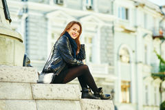 Young cheerful girl smiling posing on the steps of city street royalty free stock images