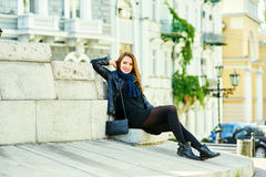 Young cheerful girl smiling posing on the steps of city street royalty free stock image