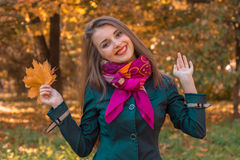 Young cheerful girl stands in the fall on the street and raised his hands up Stock Photo