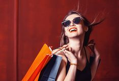 Girl with Shopping Bags. Young cheerful girl wears sunglasses holding shopping colorful bags on red background, shopaholic concept Royalty Free Stock Photo