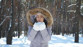 Young cheerful girl in white gloves blowing off snow from her palms. Portrait of beautiful woman standing in winter stock video