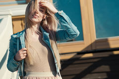 Young cheerful girl. Young blonde woman smiling in a denim jacket Stock Photos