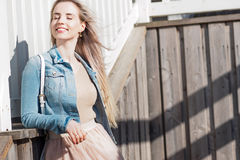 Young cheerful girl. Young blonde woman smiling in a denim jacket Royalty Free Stock Images