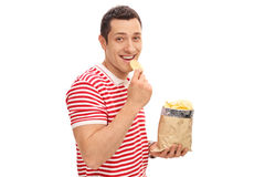 Young cheerful guy eating potato chips Royalty Free Stock Photos