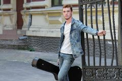 Young cheerful guy with red hair at the gate with a guitar in the case stock photography