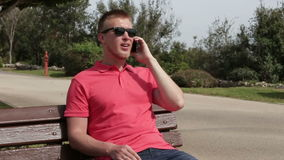 Young cheerful happy man talking using smartphone sitting on a bench in the park in the summer stock video