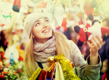Young cheerful happy woman choosing Christmas decoration Stock Images