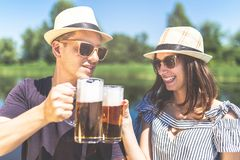 Young cheerful hipster couple with beer mugs against beautiful lake in the background stock photography