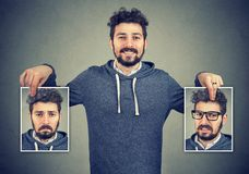 Young man having mood swings. Young cheerful hipster holding photos with different emotions having problems with mood change royalty free stock photos