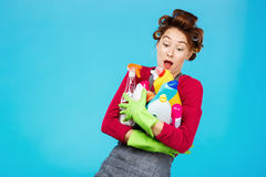 Young cheerful housewife in pink and grey holds cleaning tools Stock Photography