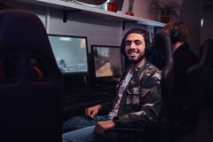 A young cheerful Indian guy wearing a military shirt sitting on a gamer chair and looking at a camera in a gaming club. A cheerful Indian guy wearing a military stock image