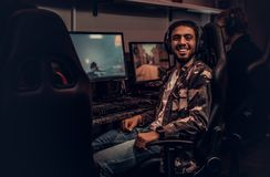 A young cheerful Indian guy wearing a military shirt sitting on a gamer chair and looking at a camera in a gaming club. A cheerful Indian guy wearing a military royalty free stock photo