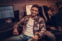 A young cheerful Indian guy wearing a military shirt sitting on a gamer chair and looking at a camera in a gaming club royalty free stock photos