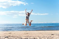 Young cheerful jumping teenage girl excitement at seaside. I Believe i can fly! Excitement of young cheerful jumping teenage girl at seaside. Blue sea with royalty free stock photo