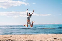 Young cheerful jumping teenage girl excitement at seaside stock image