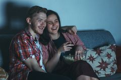 Young cheerful laughing couple watching comedy movie. With popcorn on sofa at night Stock Images