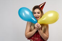 A young cheerful long-haired girl with a cap on her head and with balloons in her hands smiles happily opening her mouth. royalty free stock photo