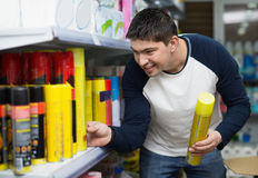 Young cheerful man choosing insects killer spray Royalty Free Stock Image