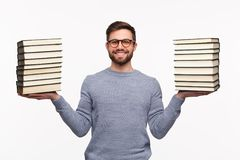 Smart student with heavy books in hands. Young cheerful man holding stacks of books and smiling at camera isolated on white Royalty Free Stock Images