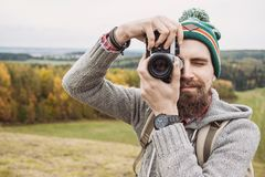 Young cheerful man photographer takes images with camera outdoors. Travel and active lifestyle concept. Young cheerful man photographer takes images with photo stock photo