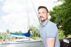 Young cheerful man relaxing on sailboat posing and looking at far on background of boats, sky and trees. Young cheerful bearded man relaxing on sailboat posing Royalty Free Stock Images