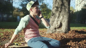 Young cheerful man with a smart phone in autumn park. stock footage