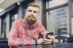 Young cheerful man using smartphone in the city. Close up of cheerful adult using mobile phone in a cafe. Young cheerful man texting on his smartphone in the royalty free stock photos