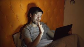Young cheerful man using tablet computer having online video chat with girlfriend while lying in bed at home before. Sleeping time stock footage