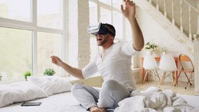 Young cheerful man wearing virtual reality headset having 360 VR video experience while sitting in bed at home royalty free stock image