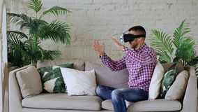 Young cheerful man wearing virtual reality headset having 360 VR video experience while sitting on couch in living room royalty free stock image