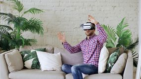 Young cheerful man wearing virtual reality headset having 360 VR video experience while sitting on couch in living room stock photos