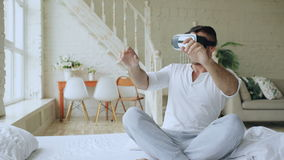 Young cheerful man wearing virtual reality headset playing 360 VR video game while sitting in bed at home stock video footage