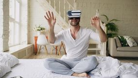 Young cheerful man wearing virtual reality headset watching 360 VR video movie sitting in the bed at home. Young cheerful man wearing virtual reality headset royalty free stock images