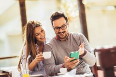 Young cheerful man and woman dating and spending time together in cafe. Young cheerful men and women dating and spending time together in cafe, using phone royalty free stock image
