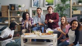 Young men having fun with video game at party in house while friends watching. Young cheerful men are having fun with video game at party in house while laughing stock footage