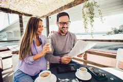 Cheerful man and woman dating and spending time together in cafe. Young cheerful men and women dating and spending time together in cafe stock photo