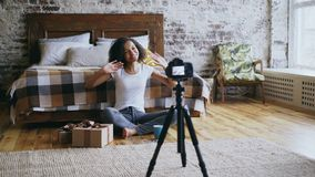 Young cheerful mixed race girl recording video blog about packing christmas gift box at home. Young cheerful mixed race girl sitting near bed recording video stock images