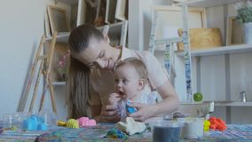 A young cheerful mother with her little child is playing with soft plasticine. Baby tries to eat plasticine. A young attractive mother with her young child makes stock footage