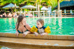 Young cheerful mother and son in a swimming pool Stock Photos