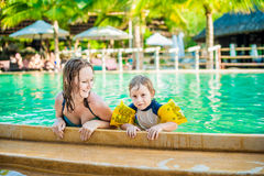 Young cheerful mother and son in a swimming pool Royalty Free Stock Image