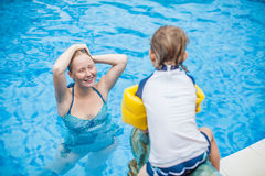 Young cheerful mother and son in a swimming pool Royalty Free Stock Photography