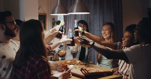 Young cheerful multiethnic friends having pizza and drinks, raise a toast together at celebration party slow motion. stock footage